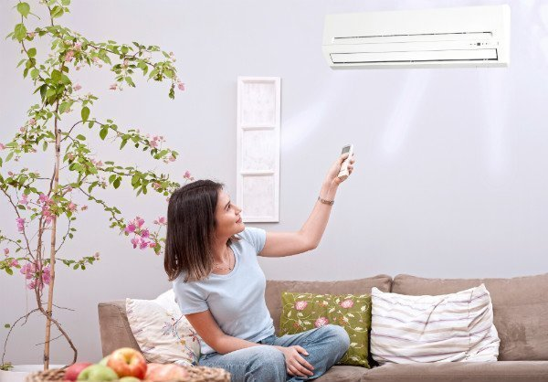 kvinde betjener luft til luft varmepumpe fra sofaen